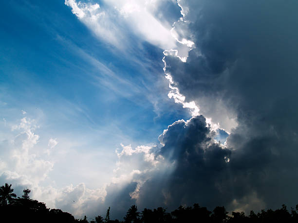 Eternal Struggle Tropical mid morning storm gathering rapidly amidst the bright sun in a clear blue sky fresh start morning stock pictures, royalty-free photos & images