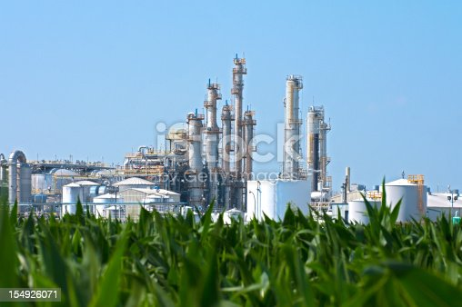 A sprawling industrial ethanol plant transforming corn as seen in the foreground into biofuel.