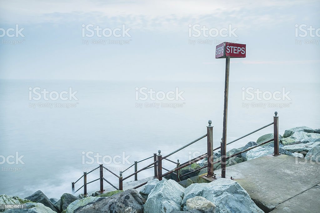 Ethereal green sea steps and red sign Whitby coast Yorkshire royalty-free stock photo