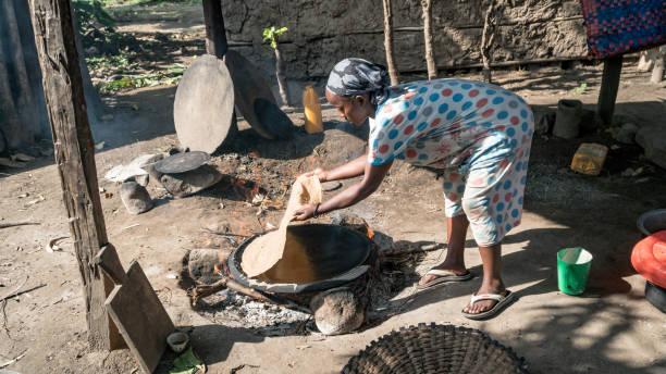 Ethiopean woman cooking Ethiopean bread called injera Omo, Ethiopia - September 2017: Ethiopean woman cooking Ethiopean bread called injera mercato stock pictures, royalty-free photos & images