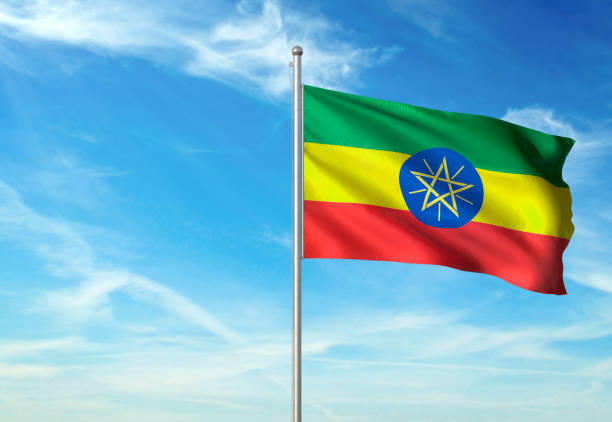 ethiopia flag waving cloudy sky background - ethiopian flag stock photos and pictures