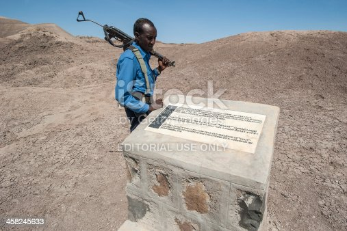 Hadar, Ethiopia - November 20, 2011: A policeman of the special Afar police unit behind the monument marking the finding place of the fossil of
