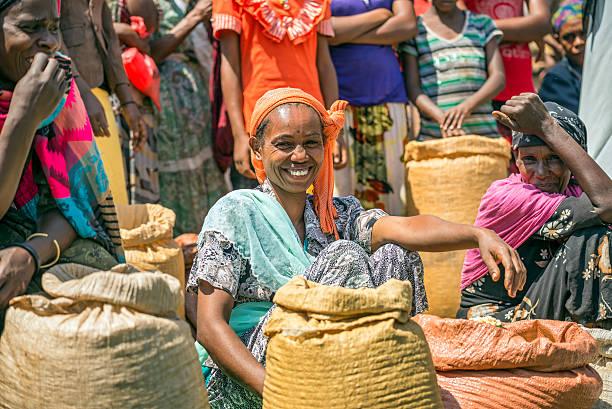 etiope donna con piante di vendita in un mercato affollato locali - mercato luogo per il commercio foto e immagini stock