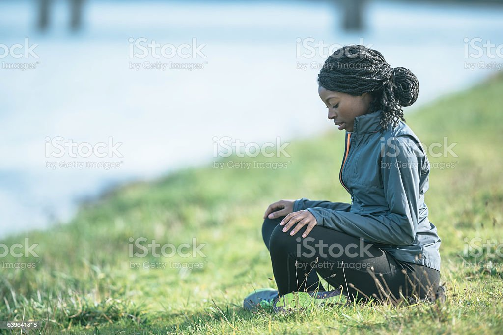 Ethnic adult female practicing meditation outdoors in nature stock photo