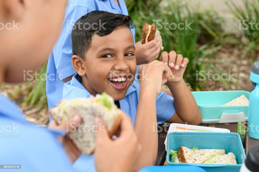 Ethnic boy eating packed lunch out side with school friends stock photo