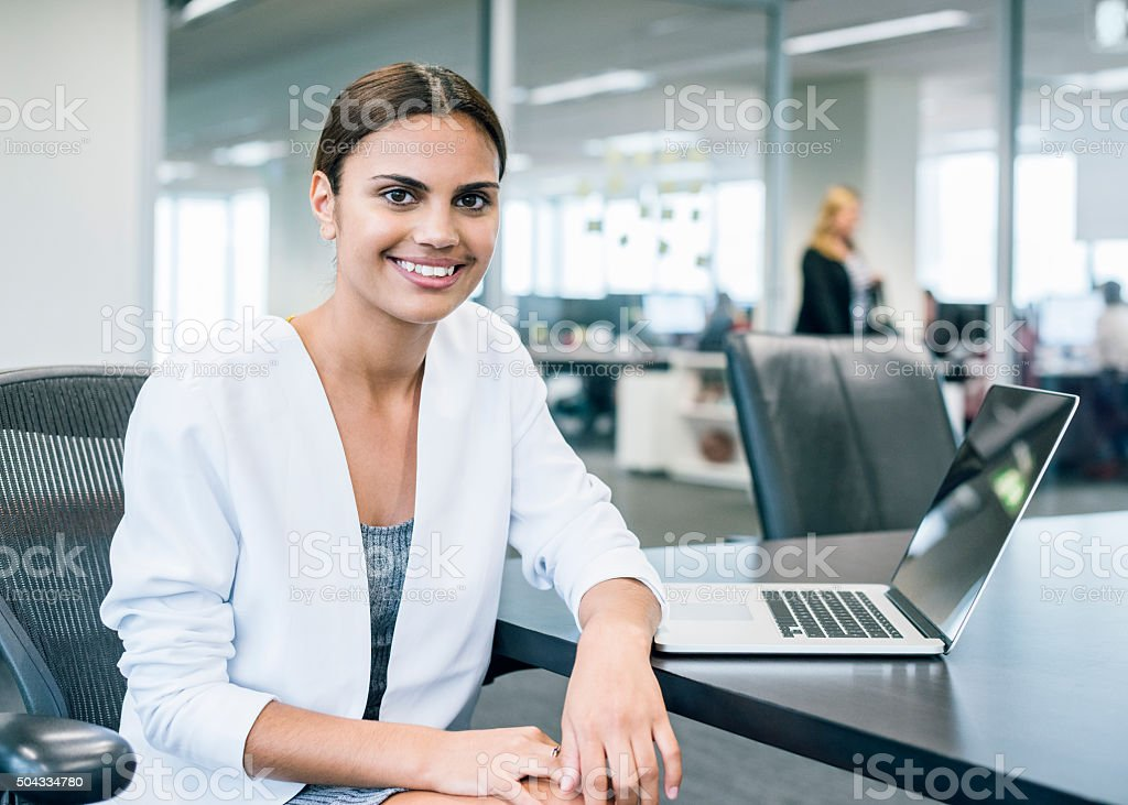 Ethnic businesswoman at desk with laptop in modern office stock photo