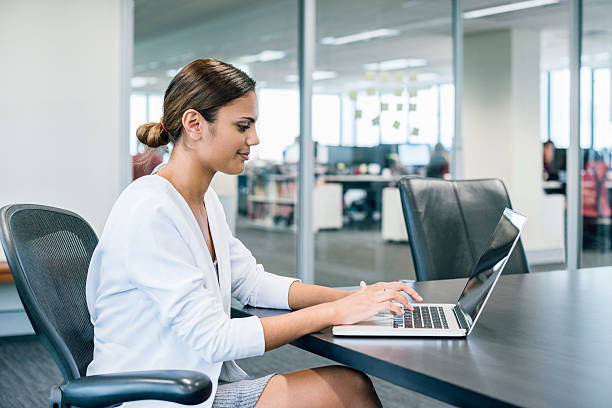 Ethnic businesswoman using laptop at desk in modern office stock photo