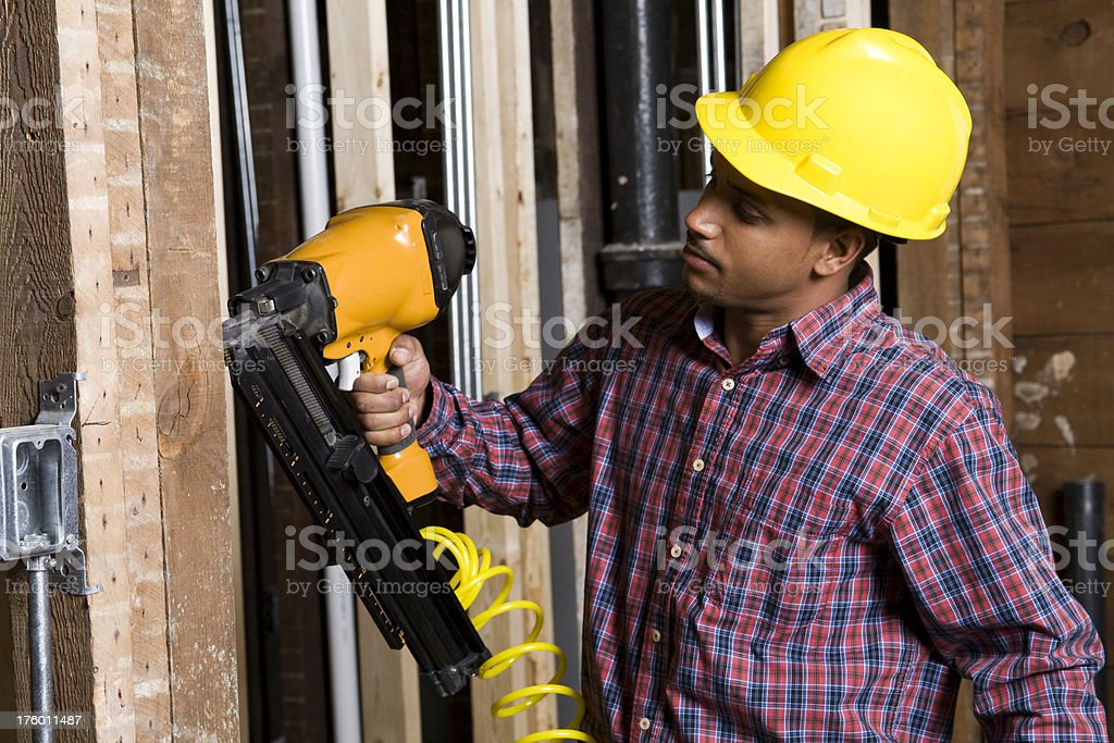 Ethnic construction worker using a nail gun royalty-free stock photo