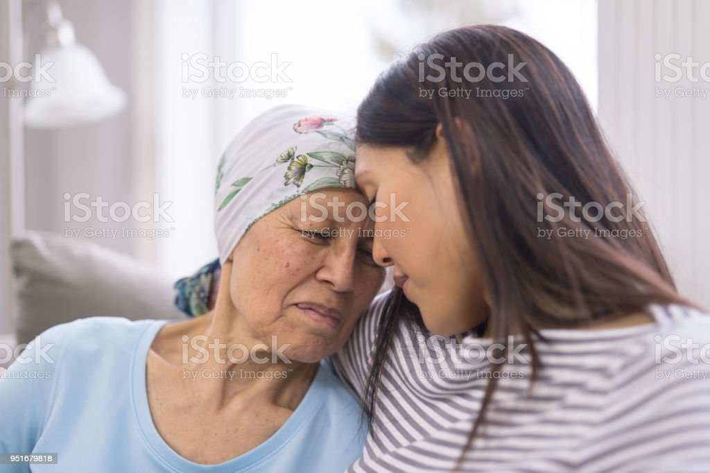 Ethnic elderly woman with cancer embracing her adult daughter stock photo