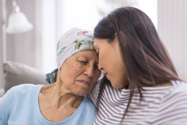 ethnic elderly woman with cancer embracing her adult daughter - cancer patient stock pictures, royalty-free photos & images