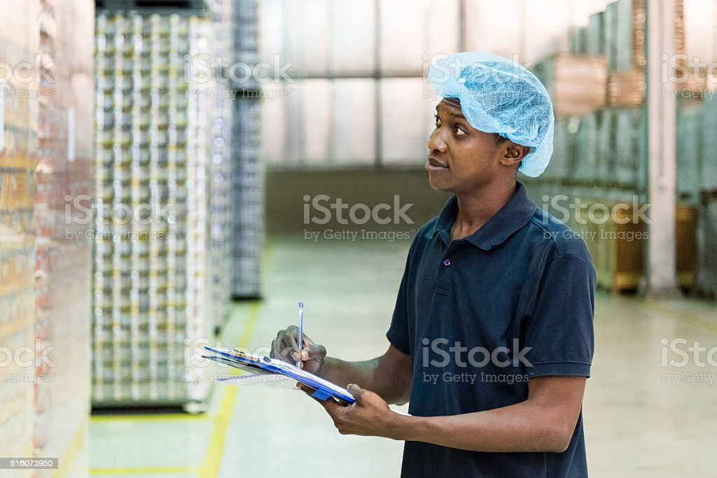 Ethnic factory worker making notes in aluminium plant stock photo