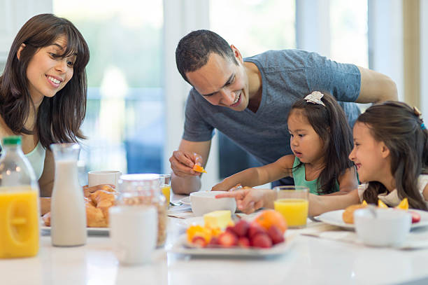 ethnic family eating breakfast together in their home - hawaiian ethnicity stock photos and pictures
