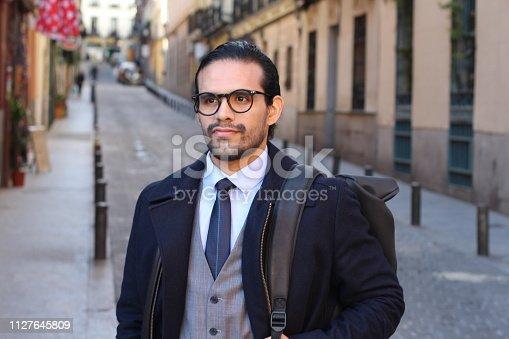 Ethnic fashionable businessman walking outdoors.