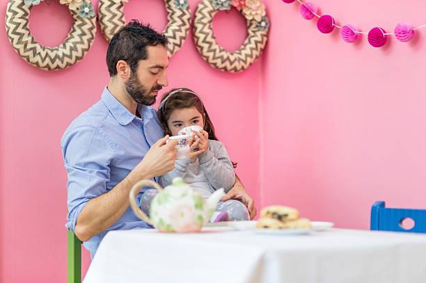 ethnic father holding his daughter on lap drinking tea - hausmannskost stock-fotos und bilder