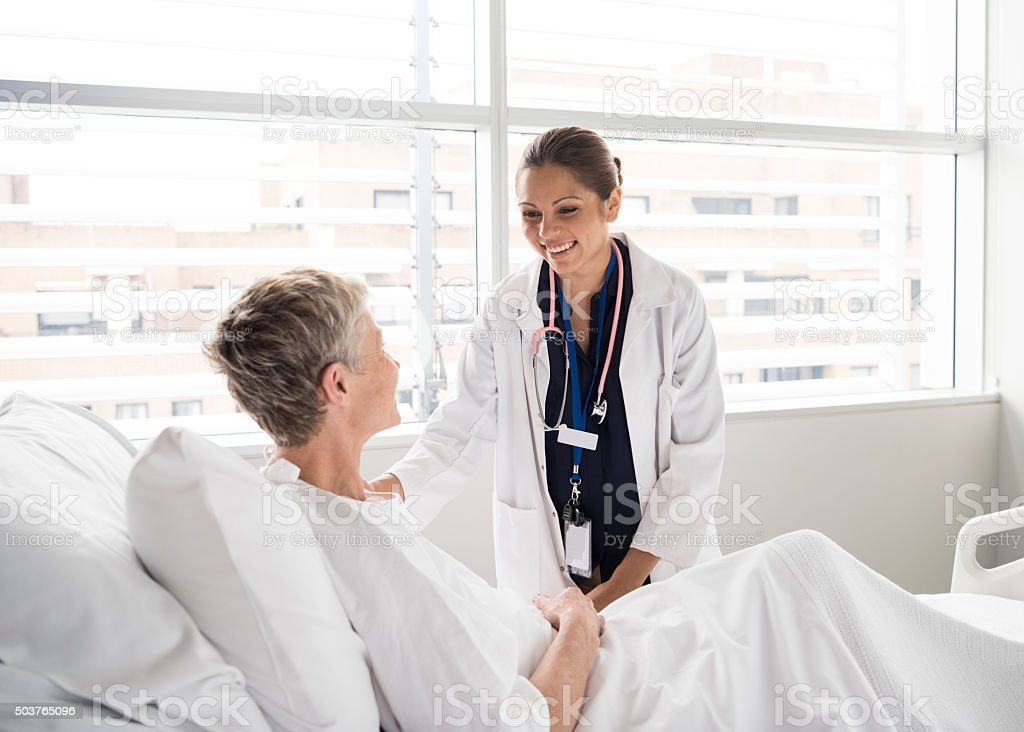 Ethnic female consultant smiling and talking with patient stock photo