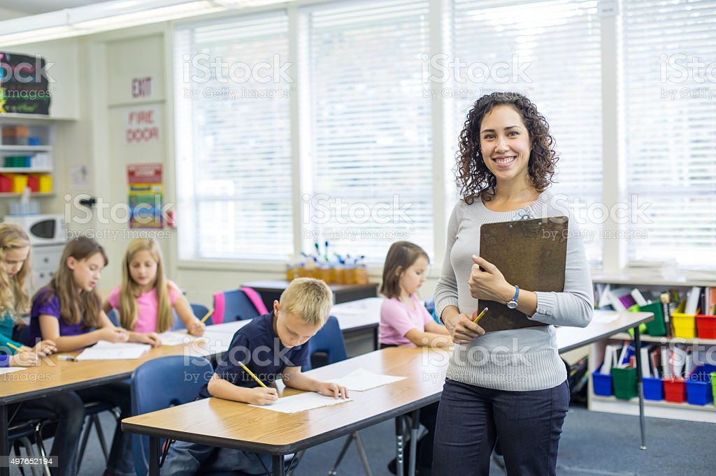 Ethnic female elementary teacher posing in front of classroom stock photo
