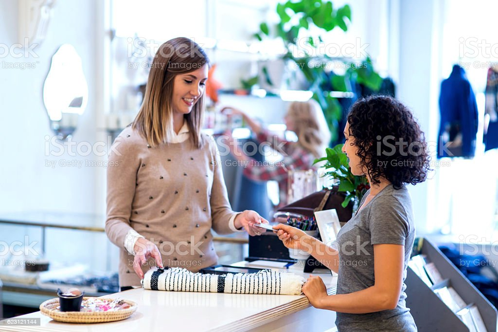 Ethnic female handing payment card over to female business owner - foto de acervo