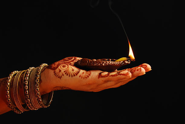 Ethnic hand with henna and gold bangles holding candle stock photo