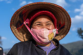 Sapa, Vietnam - march 06, 2020 : Ethnic Hmong old woman with protective mask on the face on a street of Sapa, North Vietnam