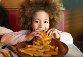 Ethnic kid girl eating burger and chips hungry at indoor restaurant