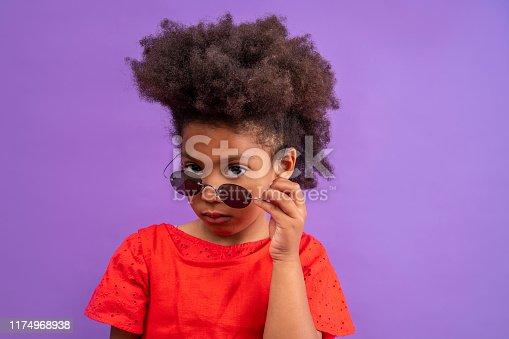 Ethnic kid girl looking camera lowering sunglasses on purple background