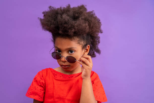 ethnic kid girl looking camera lowering sunglasses - pics for cool girl stock pictures, royalty-free photos & images