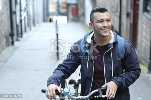Ethnic man carrying bicycle upstairs.