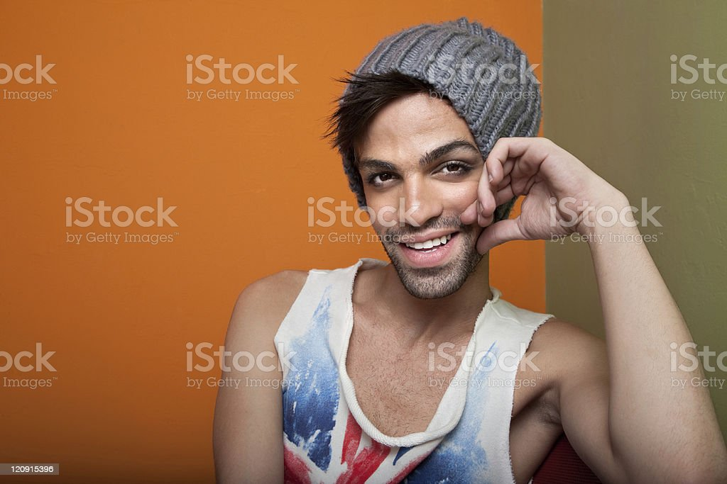 Ethnic man smiling with grey beanie, Union Jack tank top stock photo