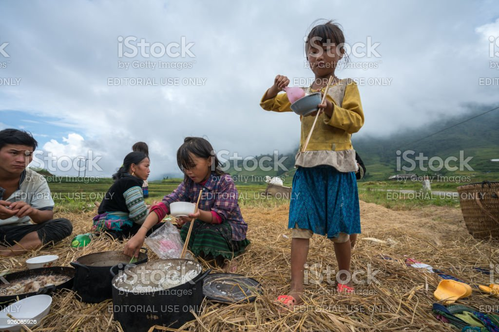 Ethnic minority farmer family having lunch on rice field in Sapa stock photo