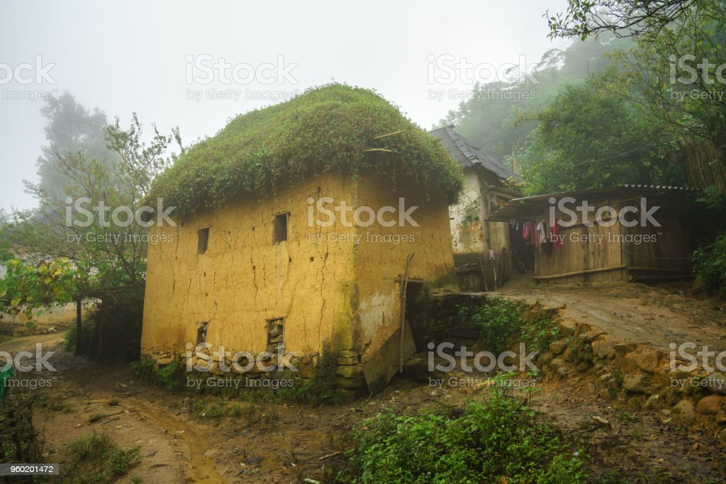 Ethnic minority Ha Nhi adobe-style thick-walled houses with mist in Y Ty, Lao Cai province, Vietnam stock photo