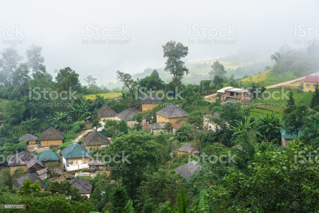 Ethnic minority Ha Nhi village with adobe-style thick-walled houses with mist in Y Ty, Lao Cai province, Vietnam stock photo