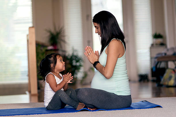 Ethnic mother and daughter meditating together on yoga mat stock photo