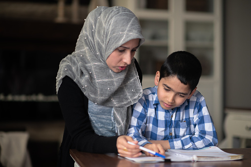 Ethnic mother helping her son with homework
