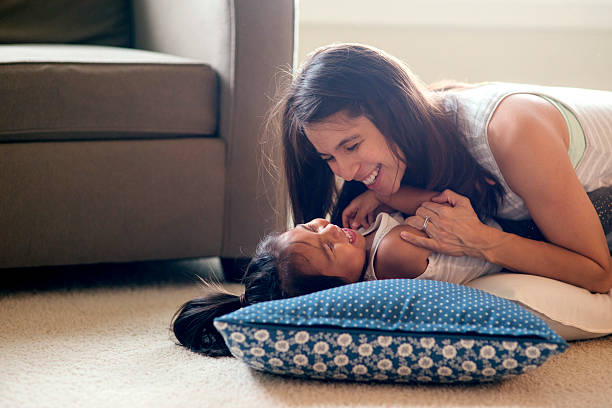 Ethnic mother tickling her cute daughter on the carpeted floor - foto de stock