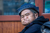 Sapa, Vietnam - march 02, 2020 : Ethnic poor old Hmong woman on the street in Sapa town, North Vietnam