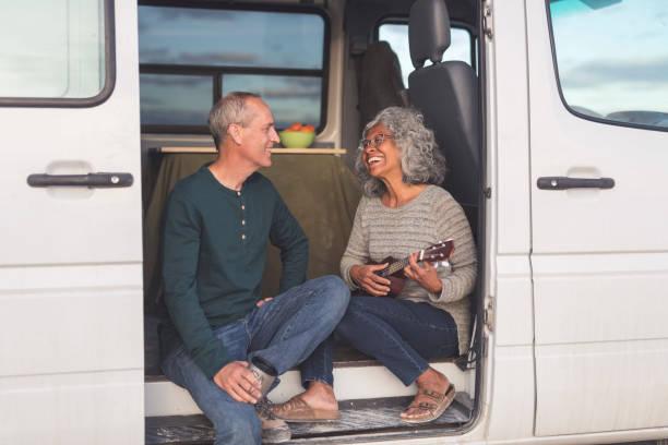 ethnische älteres paar auf einem roadtrip in ihr wohnmobil - ukulele songs stock-fotos und bilder
