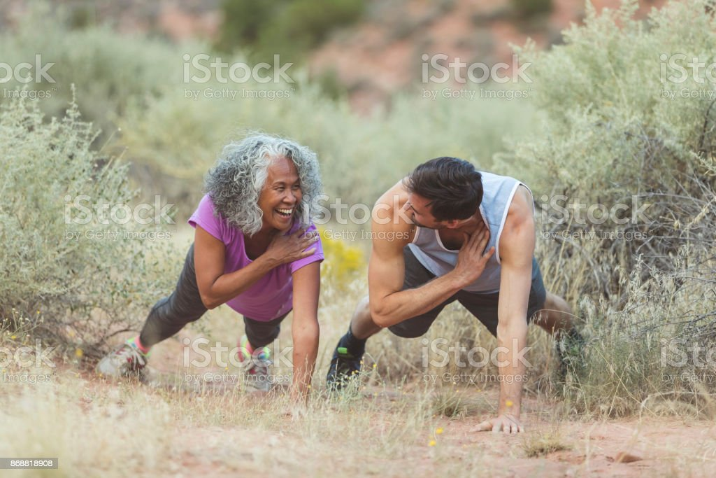 Ethnic senior woman exercising with her personal trainer stock photo