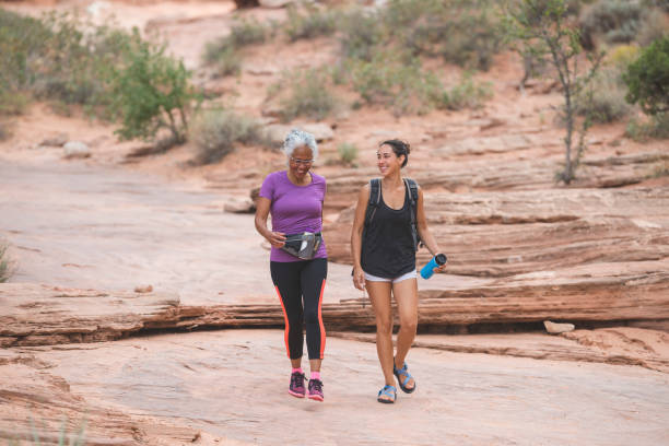 Ethnic senior woman hiking with her adult daughter stock photo