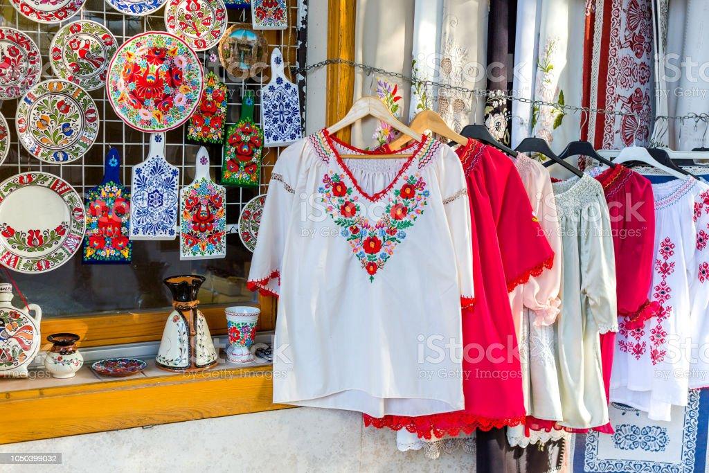 民族襯衫與傳統的匈牙利刺繡和裝飾漆板和砧板在街頭商店 - 免版稅人圖庫照片