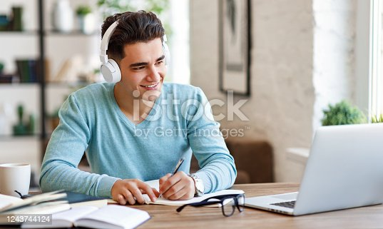 Happy ethnic guy in headphones smiling and writing in notebook while sitting at table and listening to teacher during online lecture at home