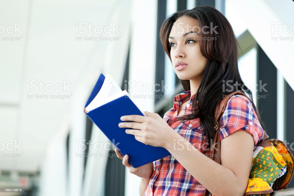 Ethnic student reading a book royalty-free stock photo