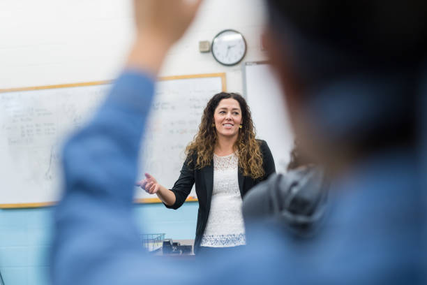 ethnic teacher points to one of her students with a raised hand - high school teacher stock pictures, royalty-free photos & images
