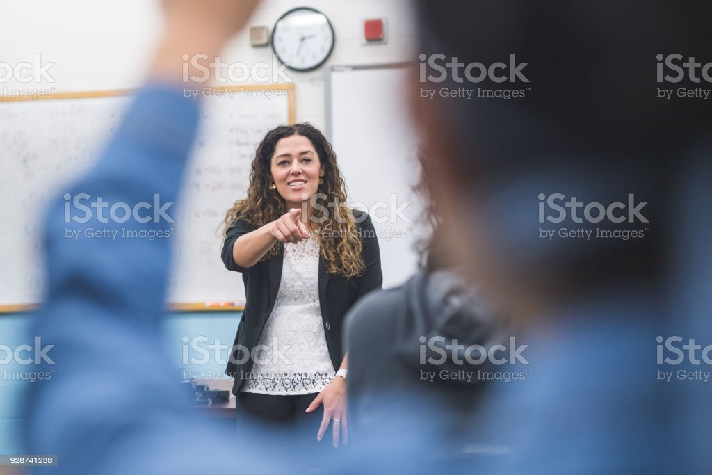Ethnic teacher points to one of her students with a raised hand stock photo