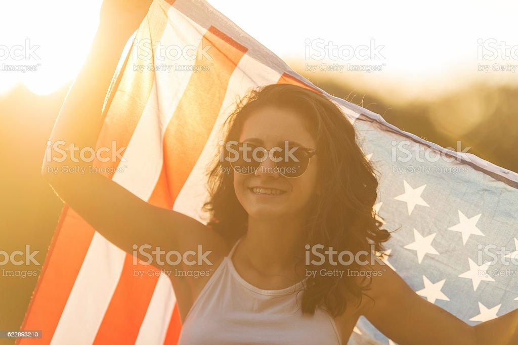 Ethnic teenage girl wearing sunglasses and holding American flag stock photo