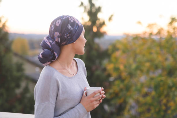 ethnic woman battling cancer standing outside and looking toward the mountains - cancer patient stock pictures, royalty-free photos & images