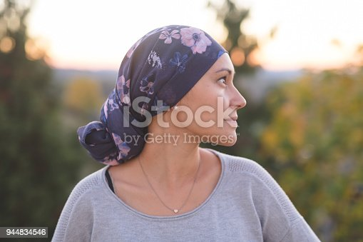 A beautiful young ethnic woman wearing a head wrap looks off-screen right and smiles radiantly. She is standing outdoors and there are mountains and trees in the background.