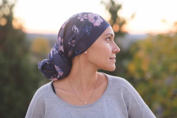 ethnische frau kämpft gegen krebs steht draußen und betrachtet ihr leben - chemotherapie stock-fotos und bilder