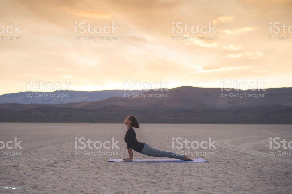 Beautiful ethnic woman does yoga in the Utah desert. She is balancing...