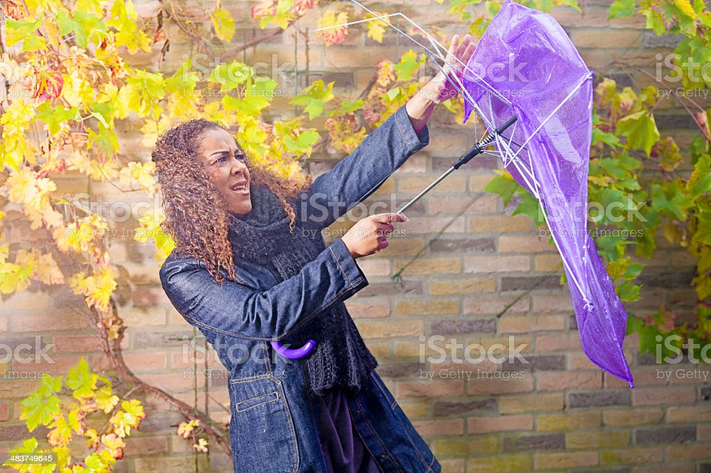 Ethnic woman fighting with her umbrella stock photo