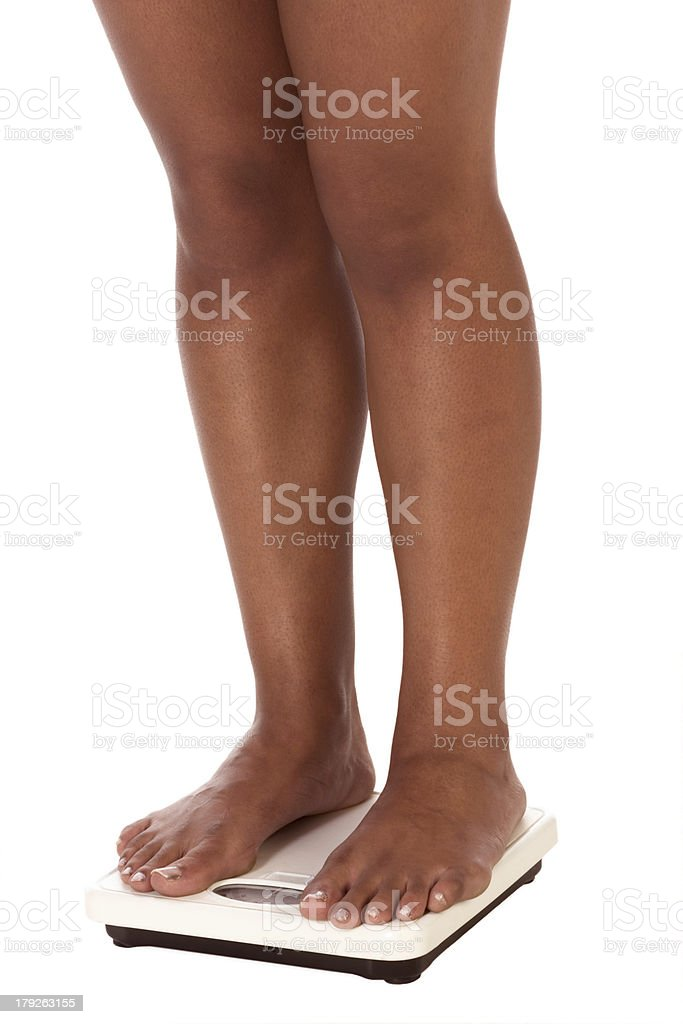 ethnic woman legs standing on bathroom scales stock photo